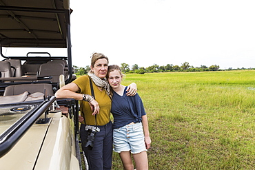 mother photographing with teen daughter near safari vehicle, Botswana