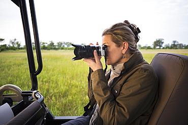 Adult woman using camera seated in a safari jeep in open landscape, Botswana
