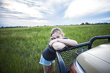 A tired teenage girl leaning on a safari vehicle, Botswana