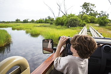 A six year old boy using binoculars looking over water from a safari vehicle, Botswana