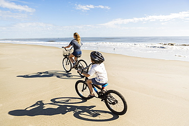 Children cycling on the sand by the water, a boy and girl, United States of America