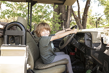 A five year old boy seated in the driving seat of a safari jeep pretending to drive, Okavango Delta, Botswana