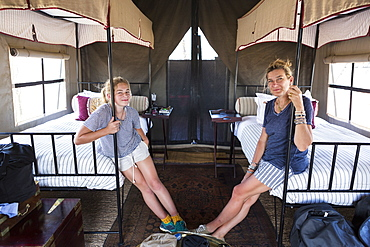 Accommodation at a wildlife reserve camp, a mother and daughter seated on beds in a tent, Okavango Delta, Botswana