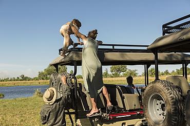 A mother and son climbing on the observation platform of a safari vehicle, Okavango Delta, Botswana