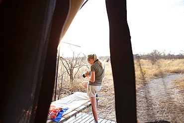 A twelve year old girl standing outside a tent at a wildlife reserve camp, using her camera, Kalahari Desert, Botswana