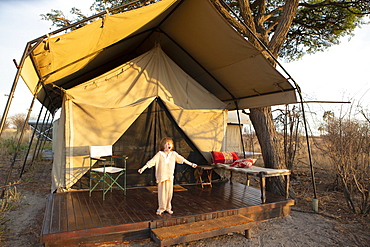 A five year old boy standing outside a tent arms outstretched, yawning yawning outside tent, Kalahari Desert, Makgadikgadi Salt Pans, Botswana