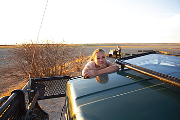 A young teenage girl on the roof of a safari jeep