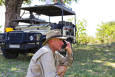 A guide in a bush hat on the radio at Moremi Game Reserve, Botswana