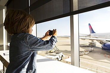 A five year old boy taking a photograph of airplane from an airport departure lounge