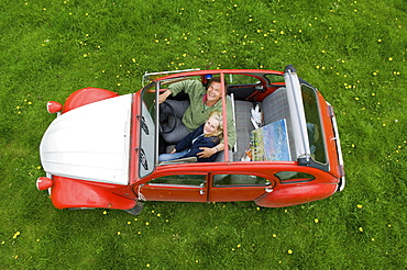 View from above of two people, a couple in a car with the roof open, Gloucestershire, England