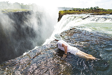 Man in the water at the Devils Pool on the edge of Victoria Falls, looking over the waterfall edge, Zambia