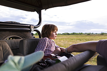 A five year old boy on safari, in a jeep in a game reserve, Botswana