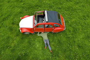A man lying on his back under a red car, inspecting the underside of the car, Gloucestershire, England
