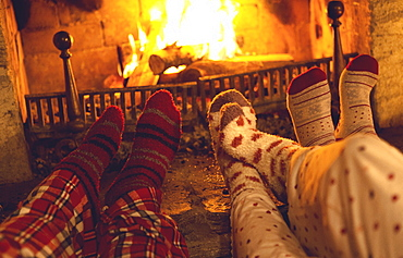 Legs and feet of three people wearing pyjamas and warm socks lying in front of a fireplace