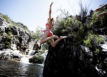 Rear view of a woman wearing a red bikini jumping into a rock pool