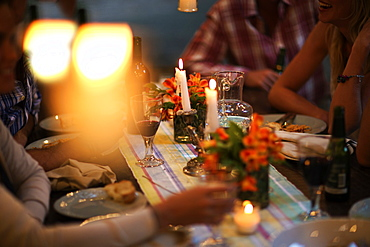 People sitting at a table with wine glasses, plates, flowers and candles