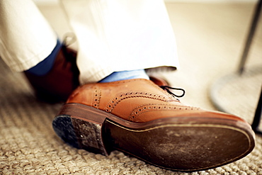Close up of person's feet, wearing brown leather brogues, blue socks and white trousers