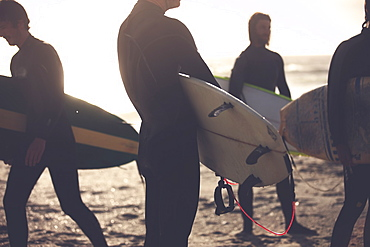 Four men wearing wetsuits standing on a sandy beach, carrying surfboards