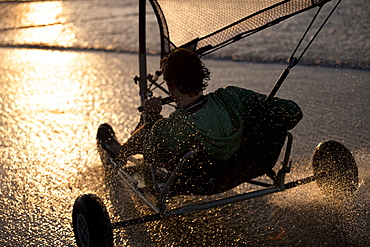 Rear view of person riding a sand yacht along a sandy beach at sunset
