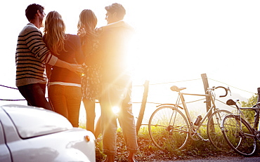 Four people standing by the side of a road, parked car and bicycles leaning against a fence, sunlight