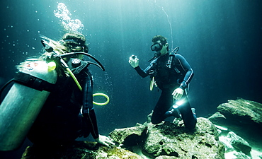 Underwater view of two divers wearing wetsuits, diving goggles and oxygen cylinders, United States of America