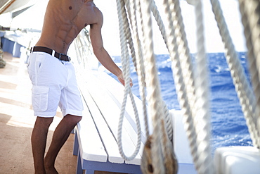 Shirtless man wearing white shorts standing on the deck of a sailing boat, rigging, United States of America