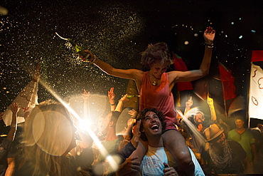 Revellers at an open air concert, smiling man carrying woman on his shoulders, arms outstretched, holding beer bottle