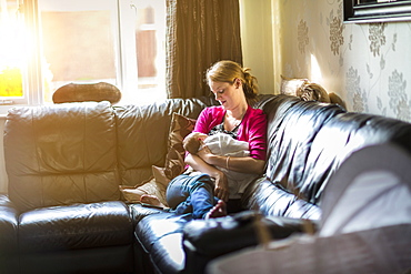 Mother relaxing with sleeping baby on sofa