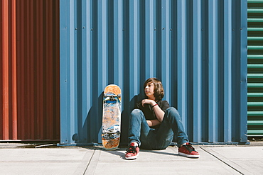 Teenage boy sitting with skateboard against warehouse wall
