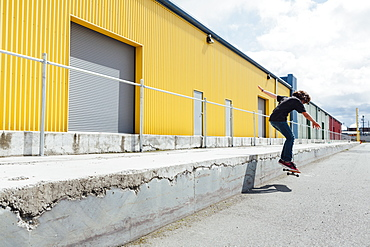 Teenage boy skateboarding in front of industrial warehouse loading zone