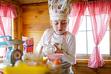 Young girl in wendy house pouring milk pretending to cook in kitchen