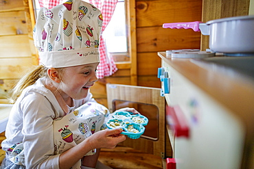 Young girl in wendy house putting cup cakes in oven pretending to cook in kitchen