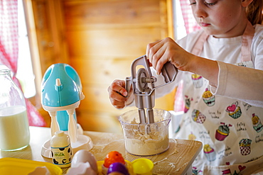 Young girl in wendy house using toy whisk pretending to cook in kitchen