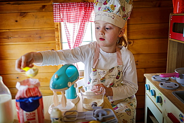 Young girl in wendy house pretending to cook in kitchen