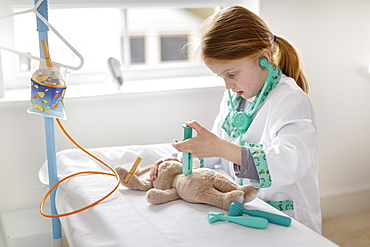 Young girl dressed as doctor pretending to treat cuddly toy in make-believe hospital bed