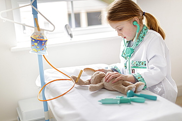 Young girl dressed as doctor pretending to treat cuddly animal in make-believe hospital bed