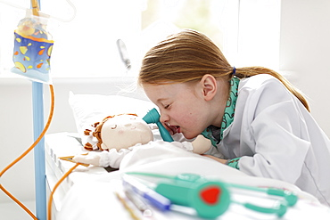 Young girl dressed as doctor pretending to treat patient in make-believe hospital bed