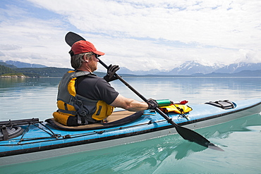 Man sea kayaking calm waters of an inlet in a national park