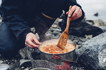 A wild camper stirring hot food in a pot cooking over a fire