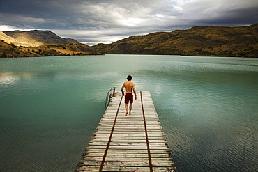 A young man walking down a wooden pier, towards calm lake surrounded by mountains in Torres del Paine National Park, Chile, Torres del Paine National Park, Chile.