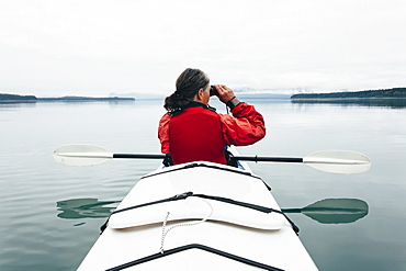 Sea kayakers looking at nautical chart and mapan inlet on the, Alaska coastline