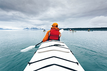 A person paddling in a double sea kayak on calm water off the coast of Alaska