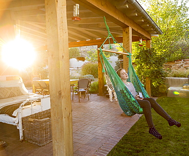 11 year old girl swinging in hammock at sunset