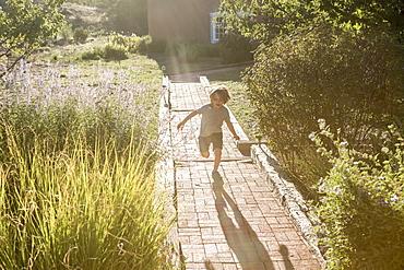 4 year old boy running on brick path