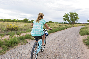 rear view of 11 year old girl biking on country road