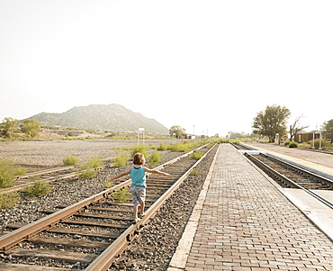 4 year old boy balancing on railroad track Lamy, New Mexico