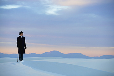 Man in a black coat and suit a bowler hat and umbrella in a white desert wilderness of white sand