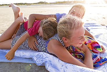 mother and her children on the beach at sunset, Georgia