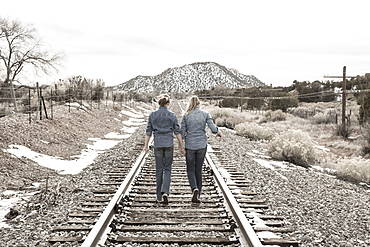 pre teen girl friends walking railroad tracks together, New Mexico