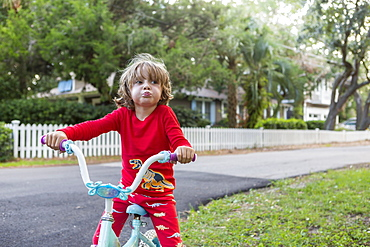 A five year old boy in a red shirt riding his bike on a quiet residential street